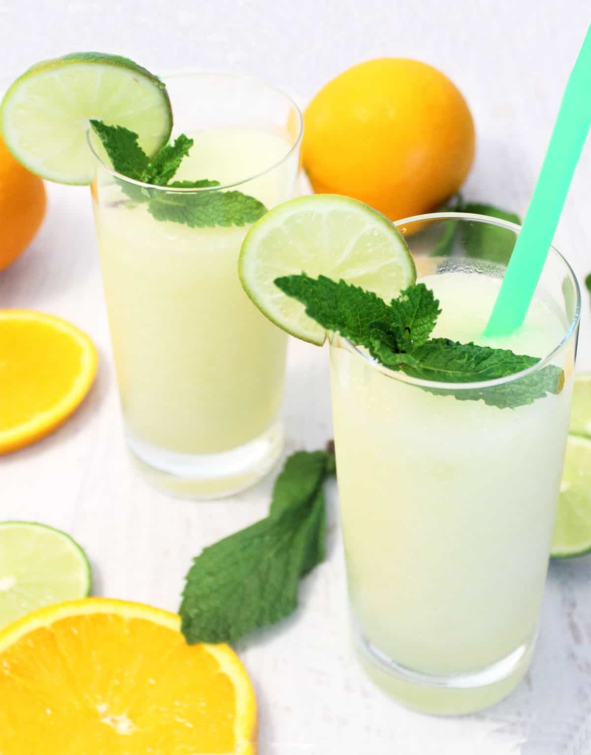 2 vodka limeades in tall glasses garnished with lime and mint.