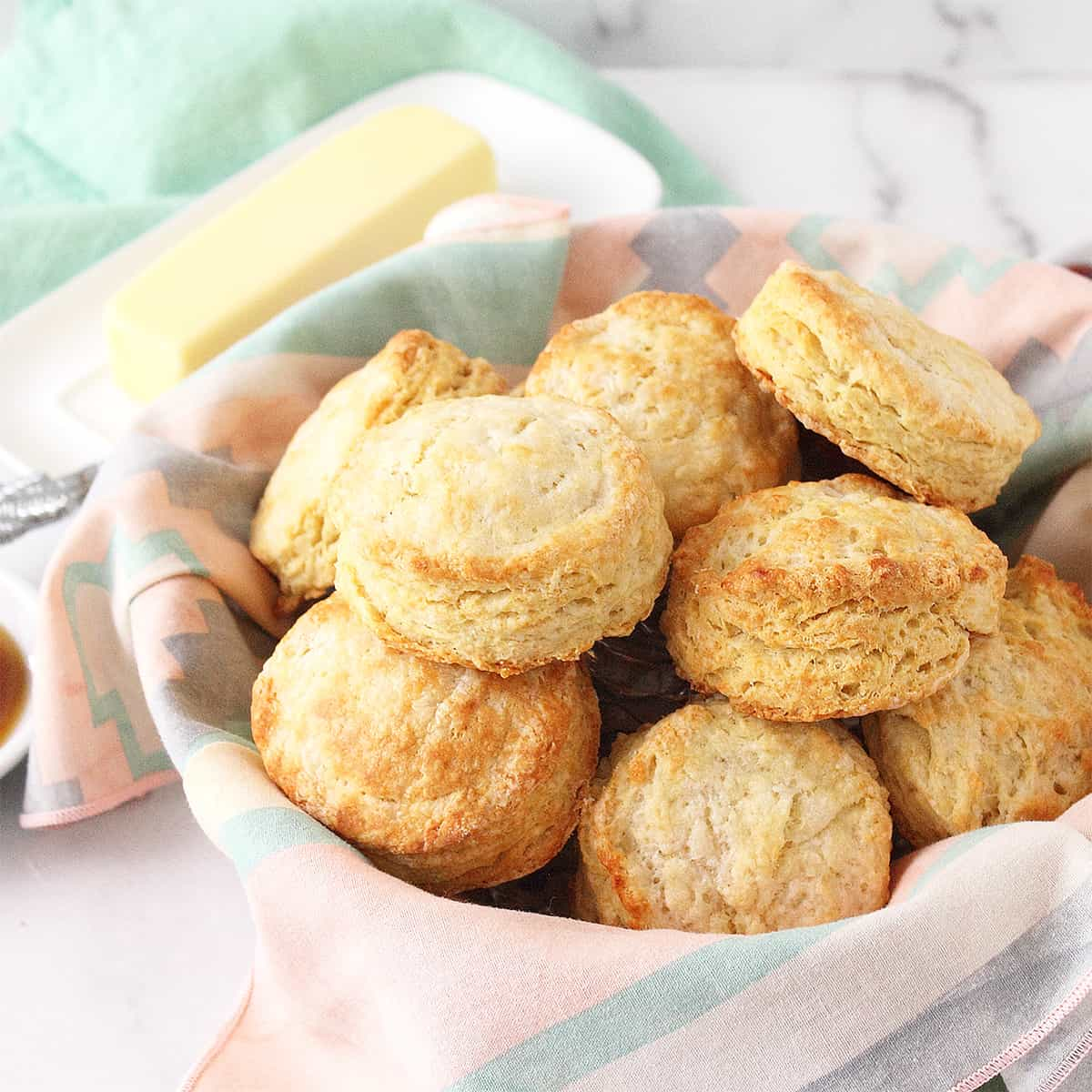Head on shot of old fashioned buttermilk biscuits in basket with napkin line and butter in back.