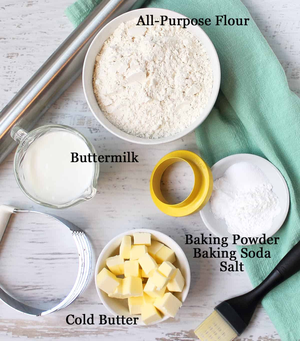 Ingredients for southern buttermilk biscuits on white table, labeled.