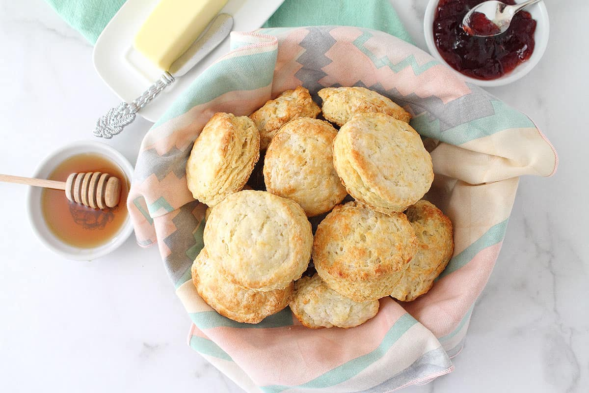 Overhead of biscuits in basket with napkin liner and jelly honey and butter beside them.