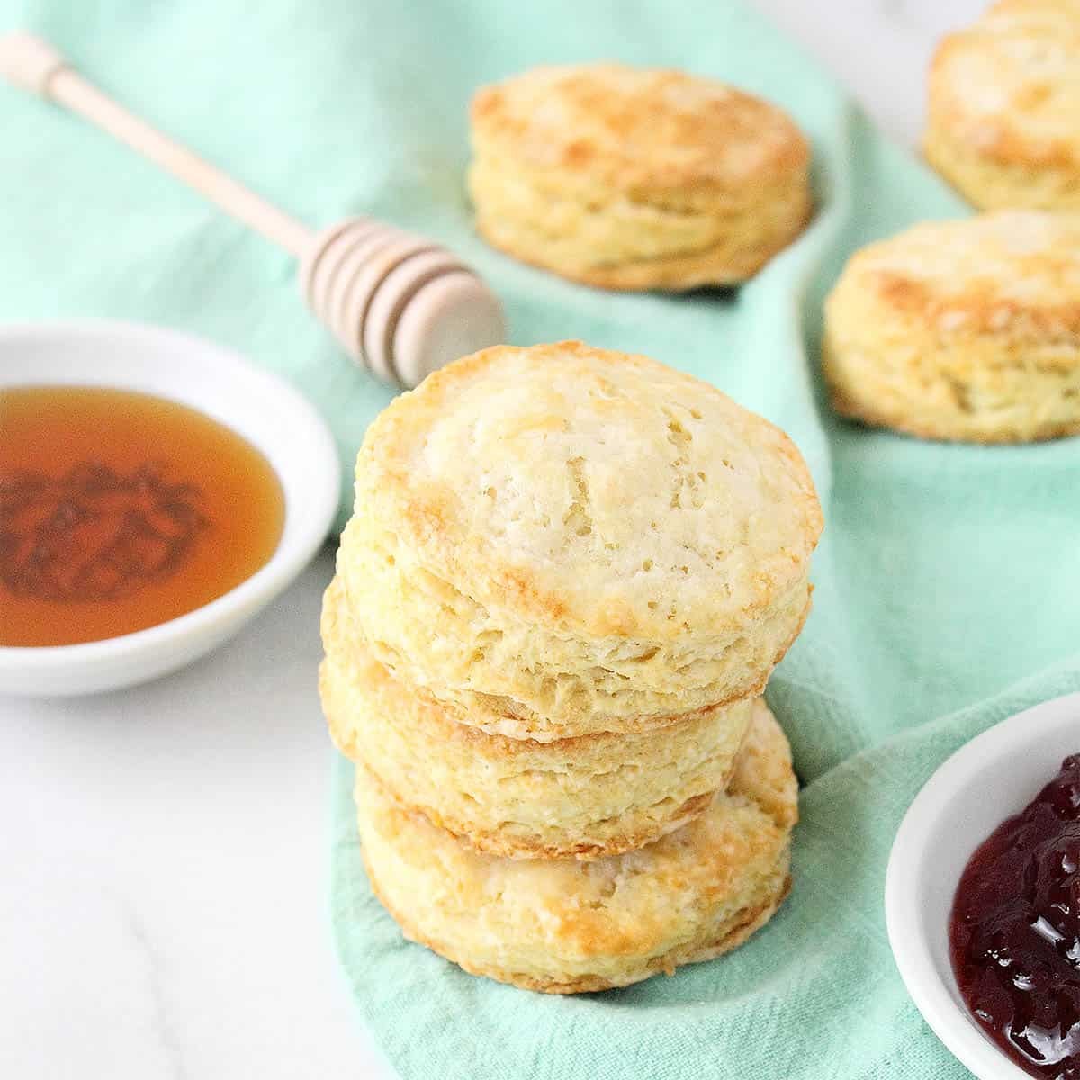 Stack of biscuits on green napkin with honey and jam beside them.