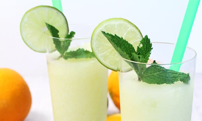 Side view of 2 cocktails with lime slice, mint and a green straw.
