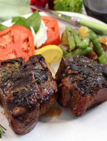 Closeup of plated lamb chops with green vegetables and caprese salad.