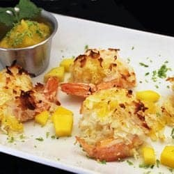 Closeup of coconut shrimp on white plate with diced mango around it.
