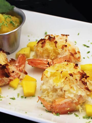 Coconut Shrimp on white plate with a small dish of mango salsa for dipping.