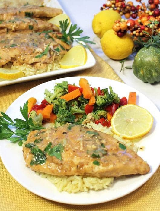 Lemon chicken on white plate with serving of vegetables.