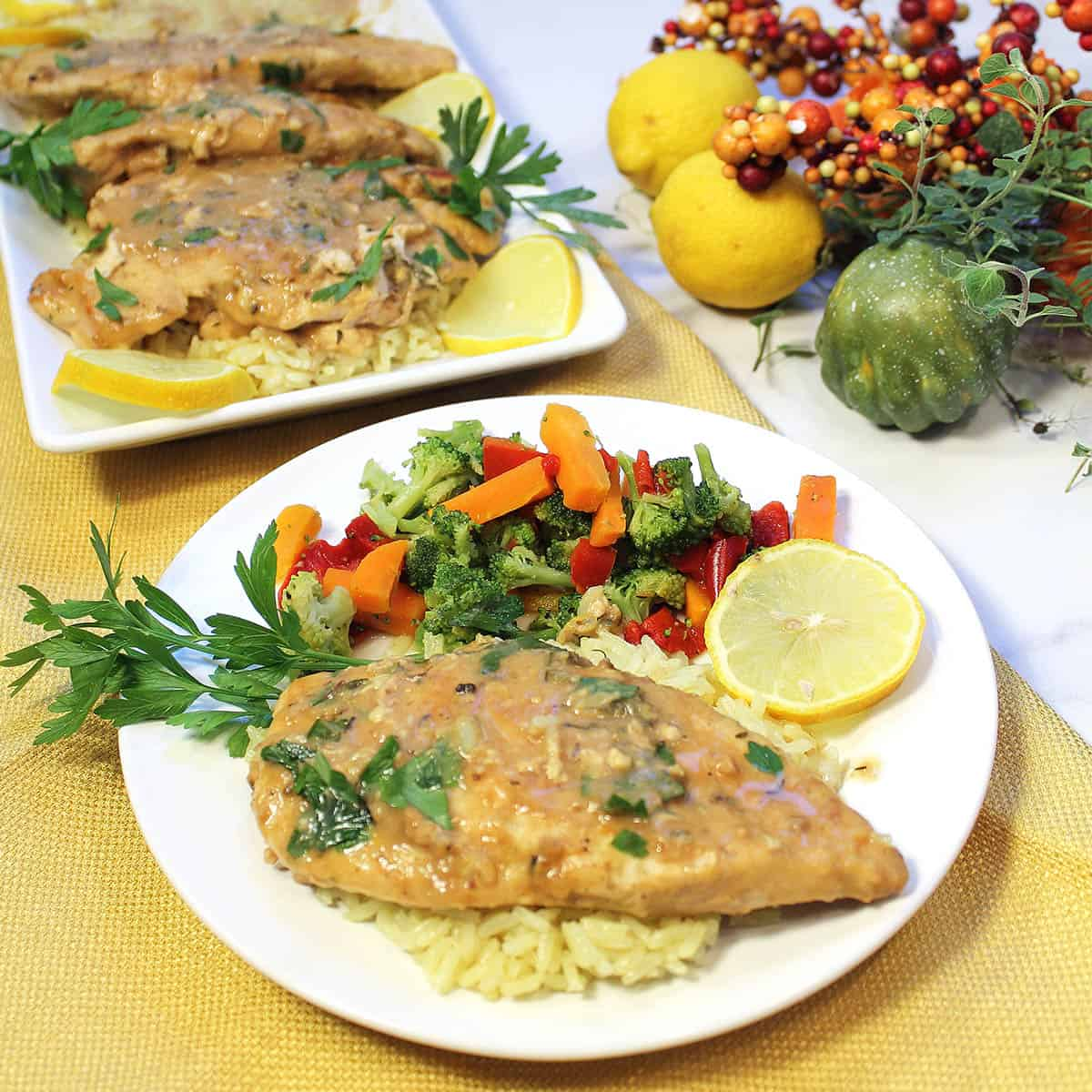 Finished chicken dinner on white plate with serving of vegetables.