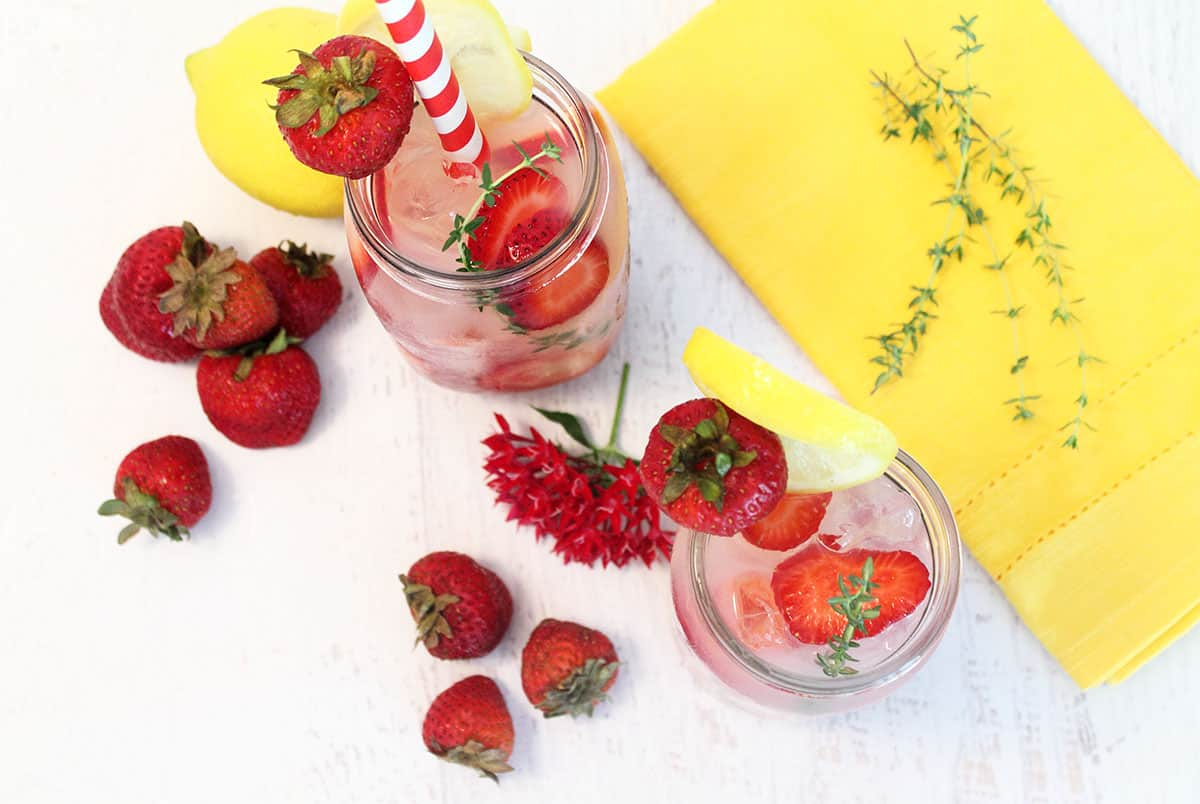 Overhead shot of filled mason jars with strawberries around it and a yello napkin with a thyme sprig on it.