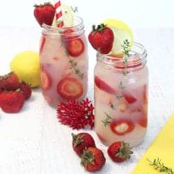 2 glasses of vodka lemonade showing sliced strawberries floating in drink with strawberries and lemon beside them.