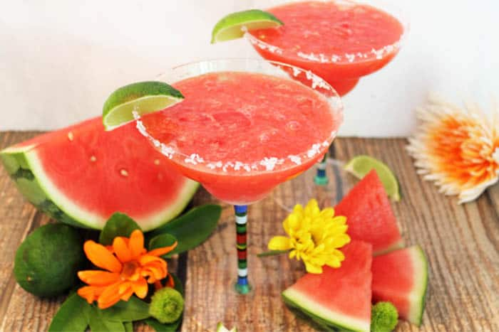 2 margarita glasses filled with frozen watermelon margarita with slice of lime and salt rim amid watermelon slices and flowers.