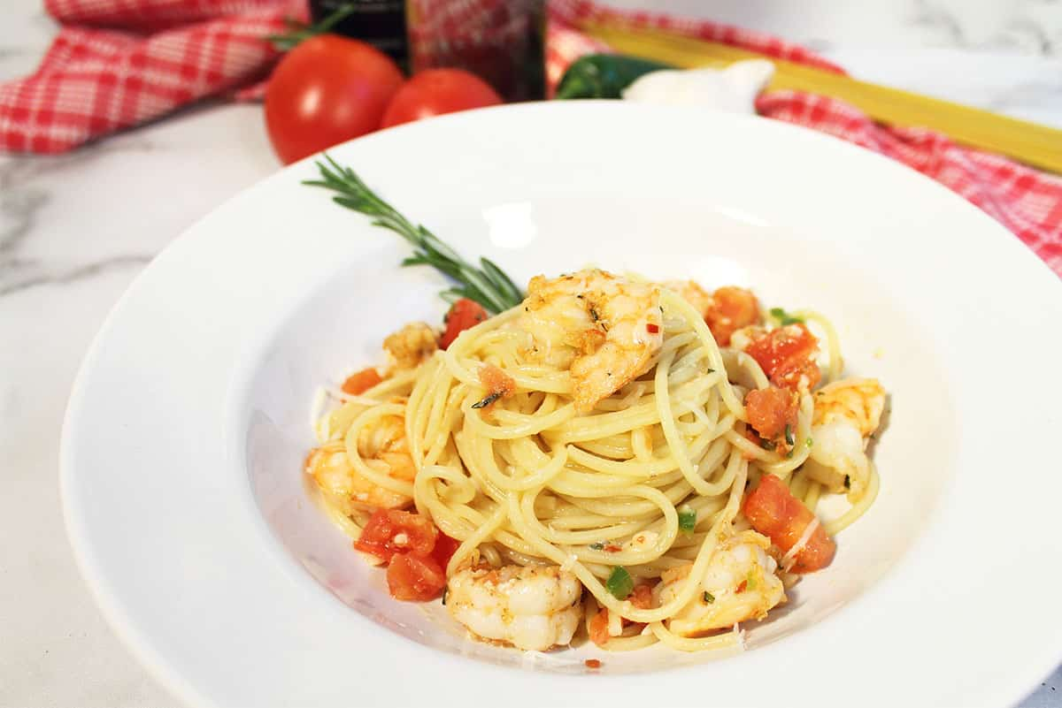 Serving of cajun pasta with shrimp in white bowl.
