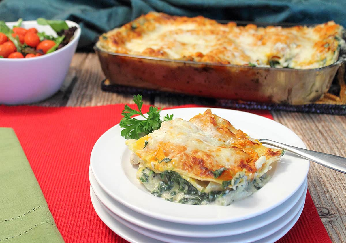 Creamy Chicken Lasagna on white plate with full casserole and salad in background.