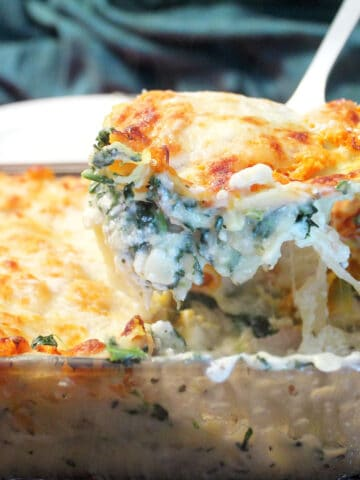 Lifting slice of creamy chicken lasagna serving out of casserole.