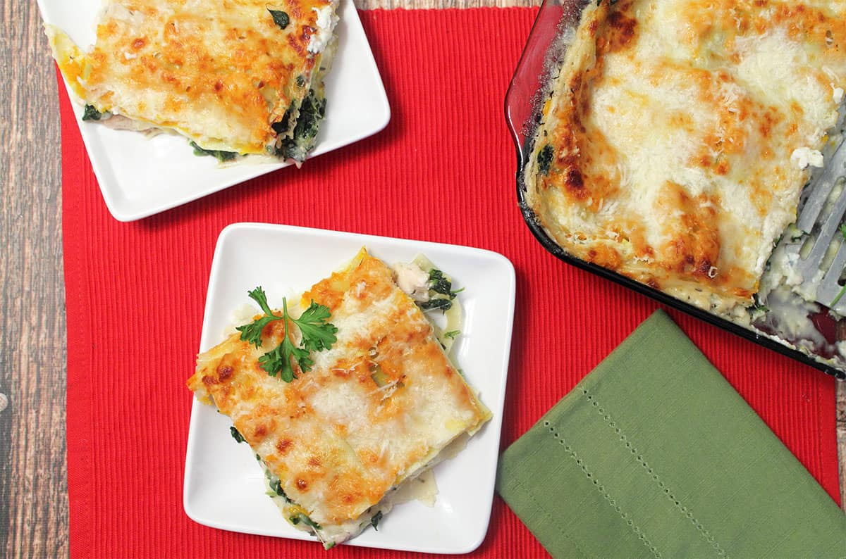Overhead of 2 servings of lasagna on white plates on red placemat with casserole on side.