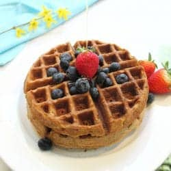 Pouring syrup on waffles on white plate.