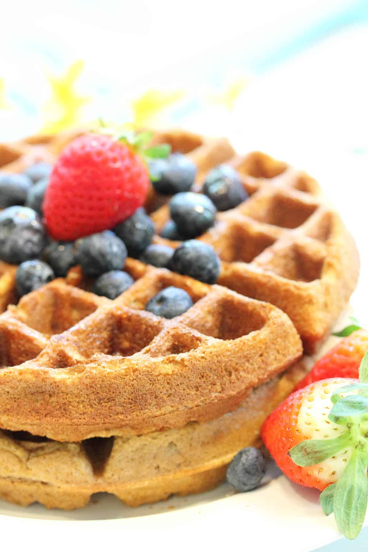 Side view of stacked almond waffles topped with blueberries and strawberry.