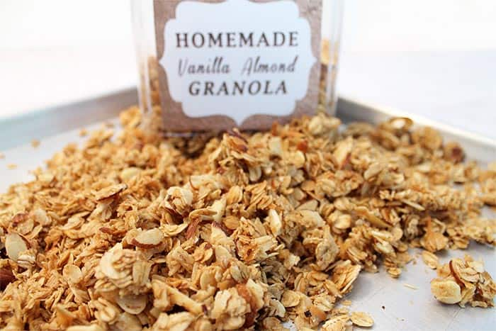 Labeled container in back of baked vanilla almond granola on cookie sheet.