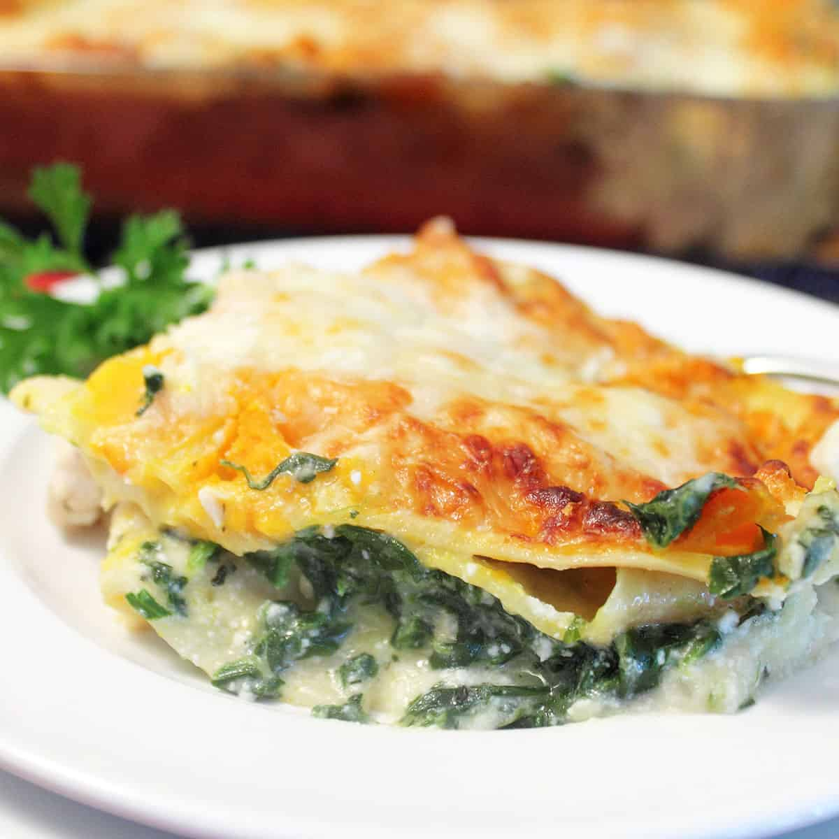 Slice of chicken lasagna on white plate showing spinach and creamy cheese sauce.