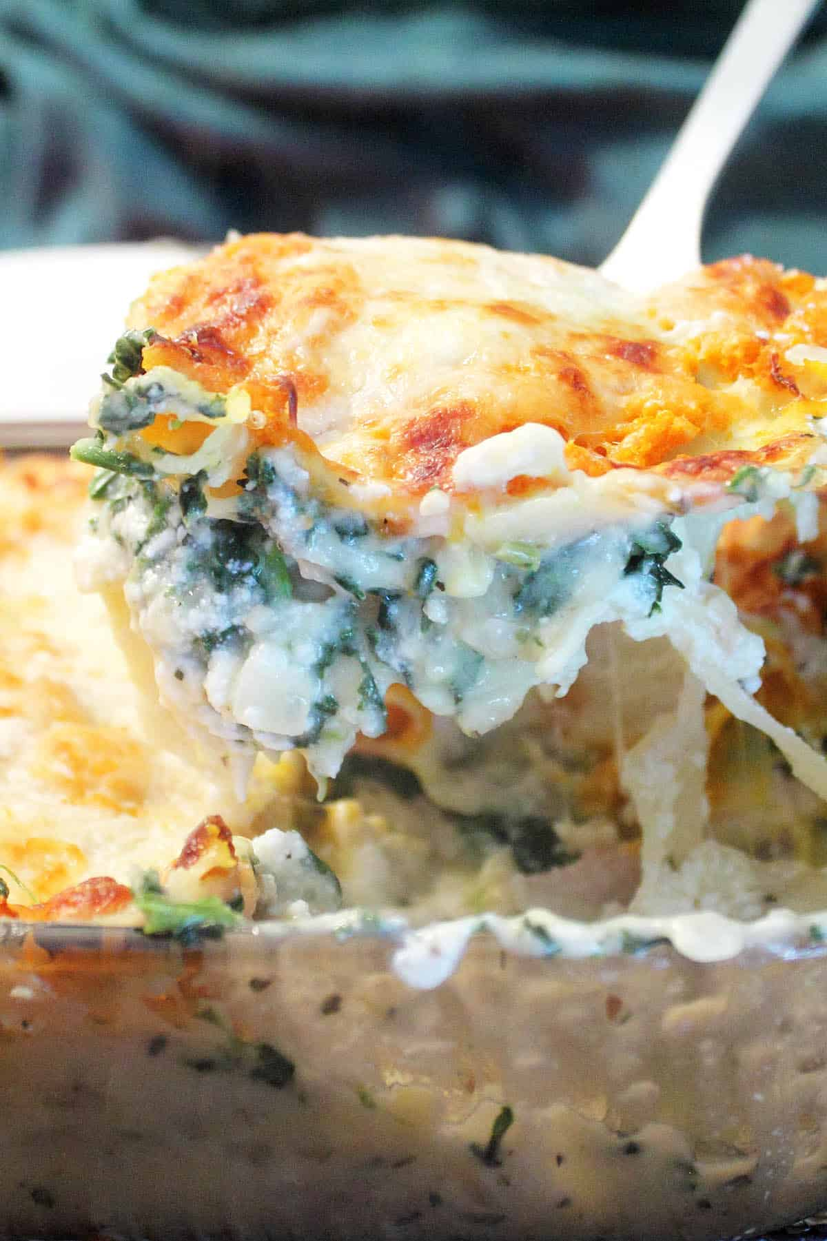 Lifting out a serving slice of chicken lasagna over casserole.