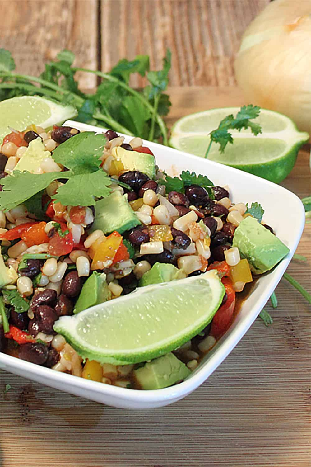 Black Bean Salad in white bowl garnished with limes and cilantro.
