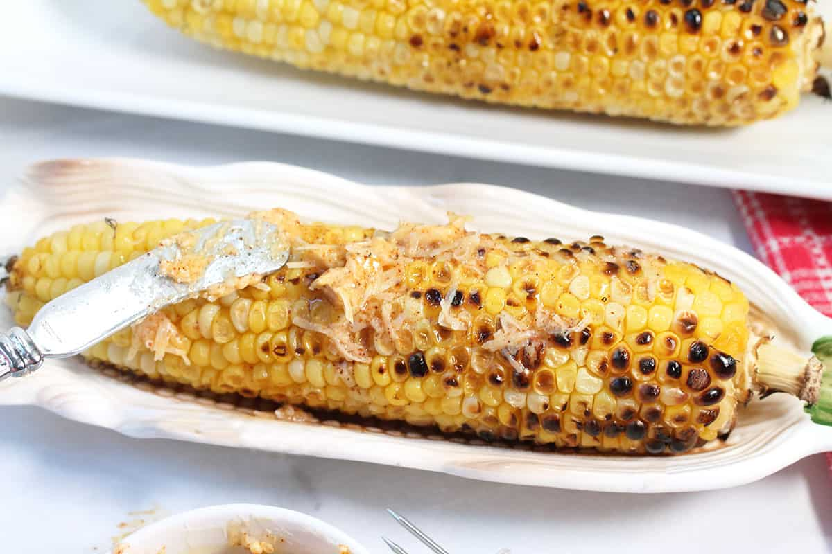 Closeup of sweet grilled corn on the cob with chili butter smeared on top.