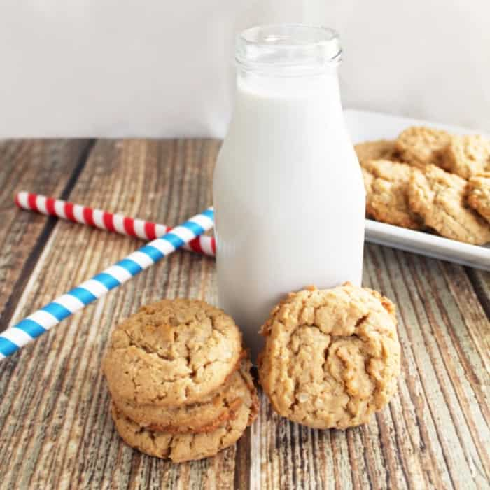 PB cookies in front of jug of milk with blue and red striped straws to side.