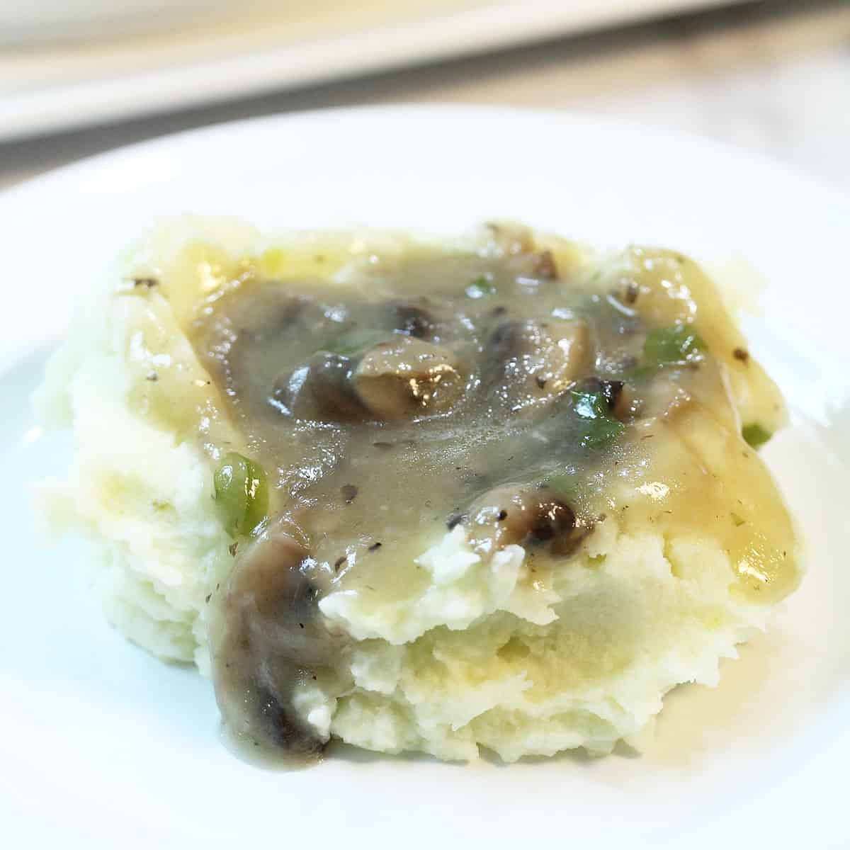Gravy topped potatoes on white plate.