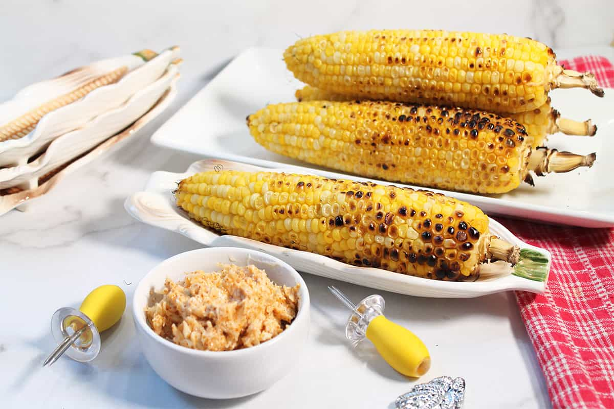Grilled Mexican corn in corn dishes with parmesan chili butter in front.