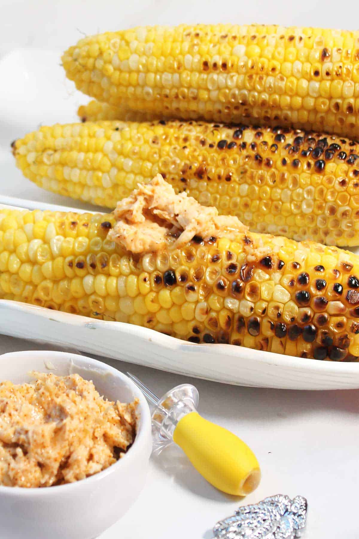 Grilled corn on cob with parmesan chili butter smeared on front ear.