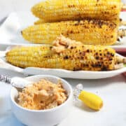 Smear of butter on sweet grilled corn in back of bowl of chili butter.