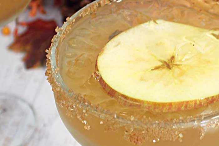 Closeup side view of Apple Cider Margarita with floating apple slice and sugared rim.