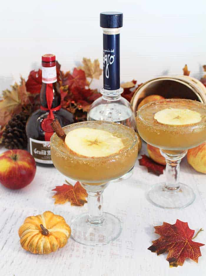 2 Apple Cider Margaritas on white table with tequila, Grand Marnier and a basket of apples and fall leaves behind them.