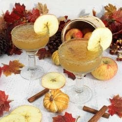 2 Apple Cider Margaritas with apple slice garnish and fall leaves behind them.