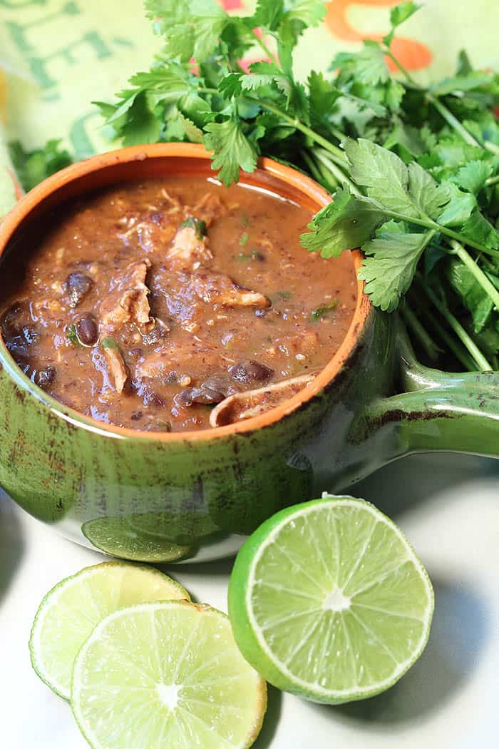 Black Bean and Chicken Soup in green bowl with cilantro and limes.