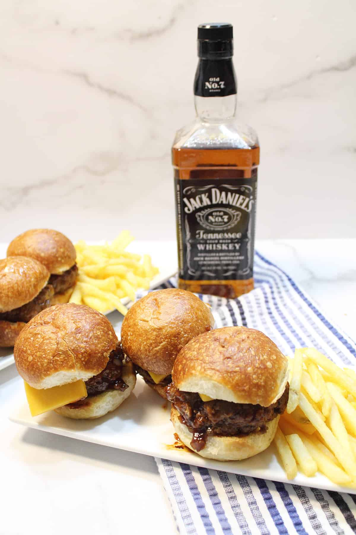 3 homemade sliders burgers on white plate with fries and whiskey bottle in background.