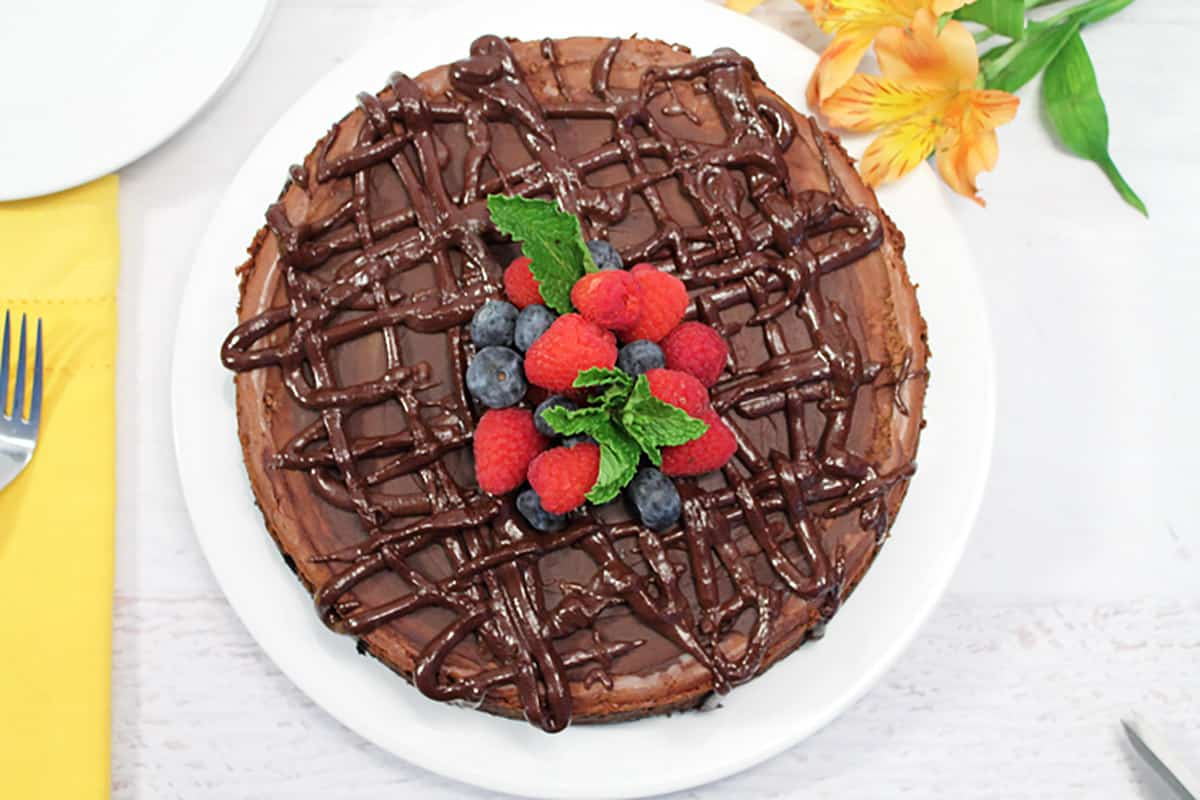 Overhead of decorated Kahlua Cheesecake on white plate.
