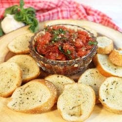 Bruschetta in crystal bowl on wood circle with bread crisps around it.