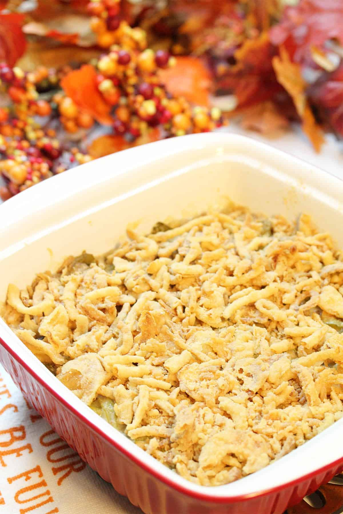 Baked creamy green bean casserole in front of fall berries and leaves.
