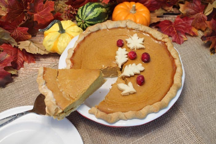 Cutting a slice of pie on pie server with gourds in backgroundamas