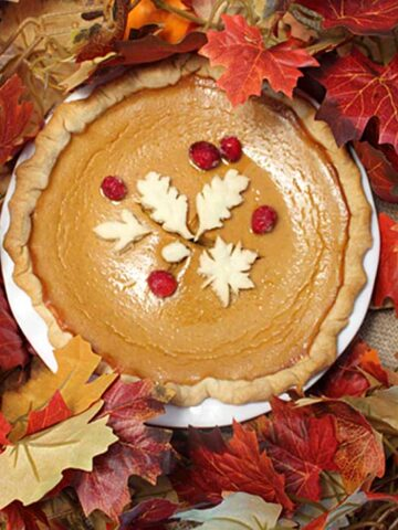 Overhead of decorated pumpkin pie surrounded by fall leaves.