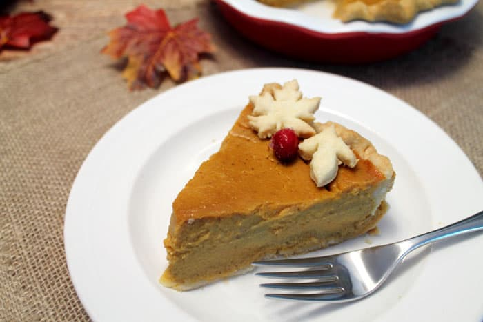 A slice of the best pumpkin pie on a white plate with fork.