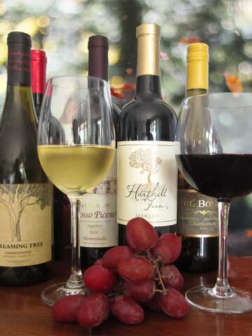 Grouping of wines with a glass of red and white wine in front.
