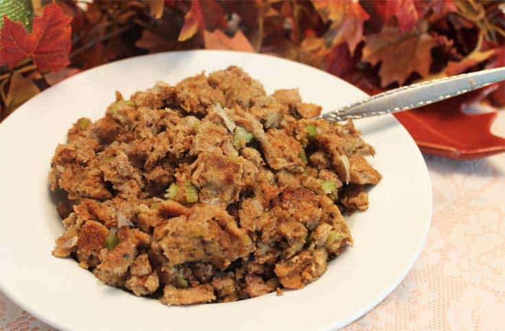 Classic Turkey Stuffing in white bowl with spoon and fall leaves behind it.