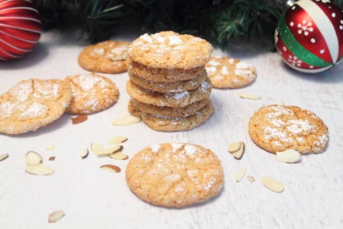 almond cookies stacked on white table with almonds around them.