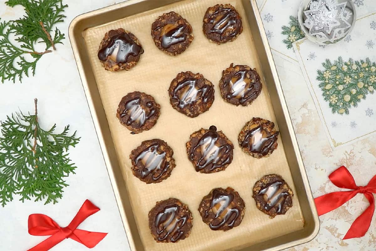 Turtle Thumbprint Cookies filled with caramel and drizzled with chocolate cookies on cookie sheet.