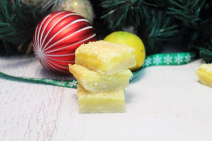 Stack of lemon squares in front of greenery and beside red ornament.