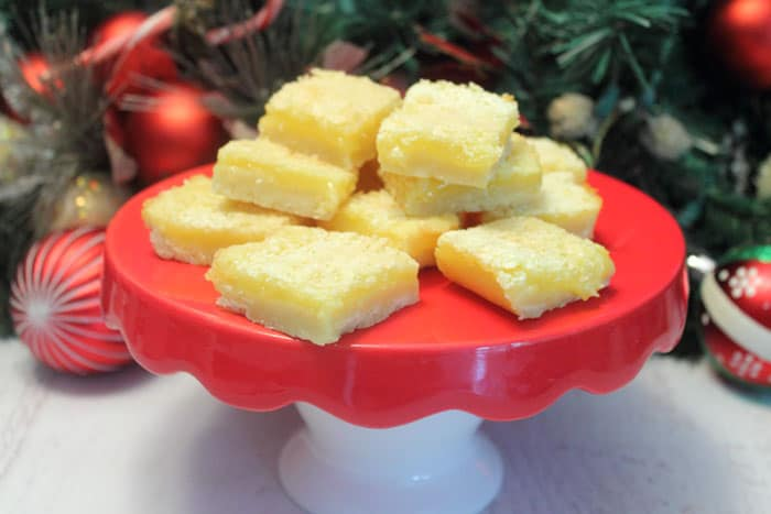 Lemon Squares stacked on red cake stand with greenery in back.