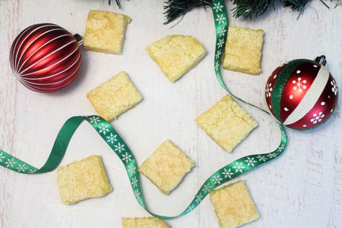 Overhead of Lemon Squares on white table with green ribbon running around them.