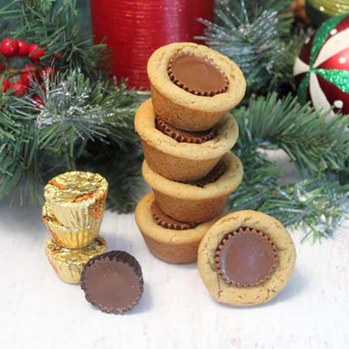Stacked Peanut Butter Cup Cookies with Christmas greenery and ornaments in background.