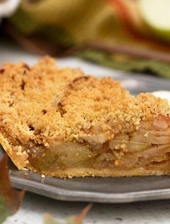 Slice of apple pie on pewter plate.